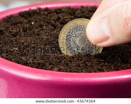 Planting a coin in a compost filled pot representing investment and savings for the future