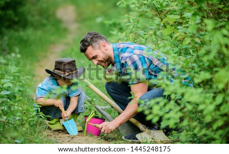 Planting flowers. Little helper in garden. Farm family. Little boy and father in nature background. Gardening tools. Gardening hobby. Dad teaching little son care plants. Spring gardening routine.