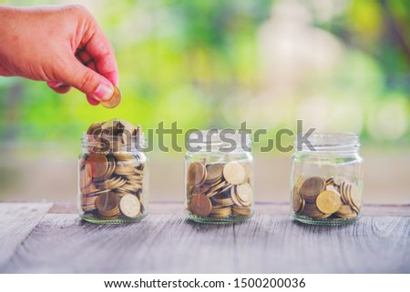 Plants and coins for watering can be used to guide financial growth and business investments. Business investment ideas for real estate concepts The concept of saving and investing a pile of risky coi