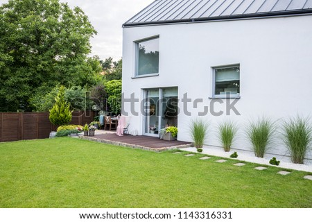 Plants, flowers and garden furniture on a wooden terrace outside of a contemporary suburban house with big windows and green grass