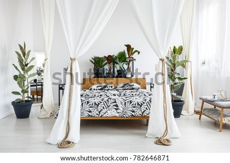 Plants on wooden bedhead of bed with patterned bedding and white drapes in bright bedroom interior with grey bench