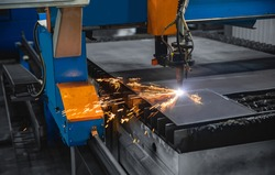 Plasma cutting CNC machine cuts metal material with sparks, industry background aerospace.