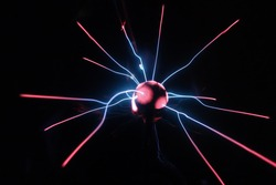 Plasma globe lamp ball in action. Blue and pink neon light effect with black background.