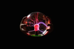 Plasma lamp wrapped by 2 hands against a black background. image. abstract shiny plasma motif