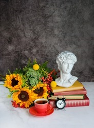 plaster copy of bust, head of antique statue, flowers, tea cup, alarm clock, books on table. back to school concept. autumn seasonal composition. fall time