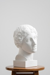 Plaster head, antique sculpture for learning to draw. Standing on a stool on a white background. Studio artist.