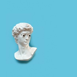 Plaster sculpture head of David with with google eyes. Gypsum copy of antique statue on blue background. modern style. creative minimal art concept. flat lay. copy space