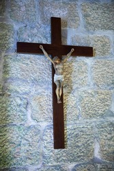 plaster sculpture of Christ crucified on a stone wall and illuminated from the side