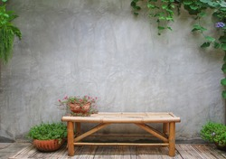 plaster wall backdrop with bamboo bench in garden