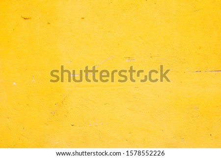 plastered old wall painted yellow textured paint with scratches and damage
