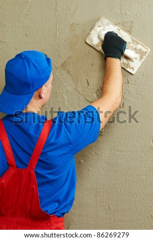 Plasterer at indoor wall renovation decoration with float