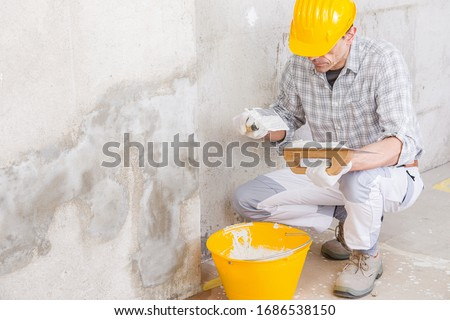 Plasterer covering a stained damp patch in a white wall with new plaster or masonry during renovations or maintenance on a house interior ストックフォト ©
