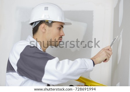 plasterer filling the holes on the wall #728691994