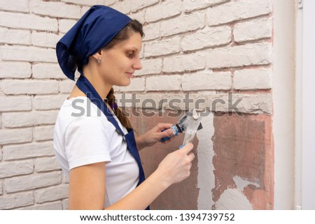 Plasterer girl plasters a wall, laying out imitation brickwork #1394739752