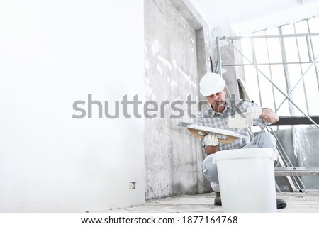 plasterer man at work, take the mortar from the bucket to plastering the wall of interior construction site wear helmet and protective gloves, and scaffolding on background