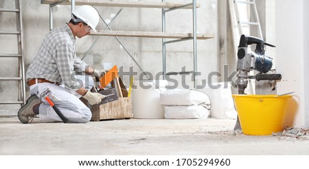 plasterer man construction worker work with tool box wear gloves, hard hat and protection glasses at interior building site with scaffolding. bucket, sacks and jackhammer Сток-фото ©