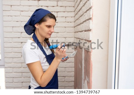 Plasterer plasters the wall, causing it to imitate brickwork #1394739767