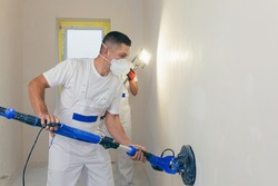 Plasterer smoothes the wall surface with a wall grinder. Two master builders grind a white plaster wall. a man in overalls grinds the surface in a respirator. experienced repairman