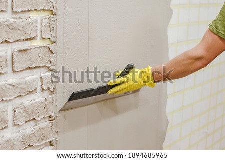 Plasterer smoothing  plaster  on wall for making texture of torn brick made of cement plaster by hand. Tape under plaster on wall to imitate decorative brick. home repair