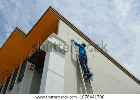 Plasterer stand on stair and making plaster by trowel at bangkok,Thailand #1078441700