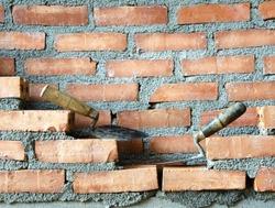 Plastering trowel tool for brick laying on orange.