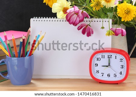 plastic alarm clock, bouquet, textbooks, pencils and open album. blank page for your text. September 1, knowledge day, back to school. Teacher's day.