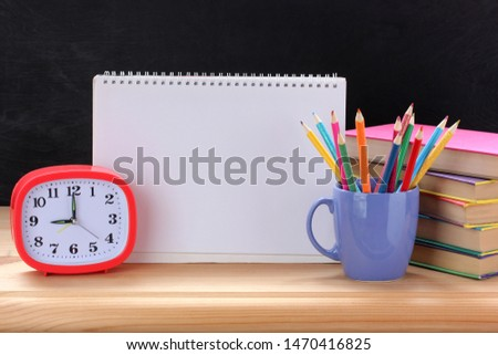 plastic alarm clock , textbooks, pencils and an open album. blank page for your text. back to school.