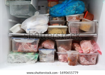 Plastic bags and container with frozen food in freezer refrigerator background.