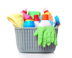 Plastic basket with domestic desinfectant bottles and sprays.Household item isolated on white.Housekeeping object.