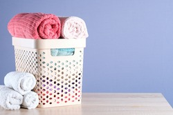 Plastic basket with rolled bright towels on the table, grey isolated. Copy space.