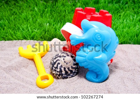Plastic beach toys on sand with shell