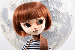 Plastic big eyes doll portrait with moon sky background