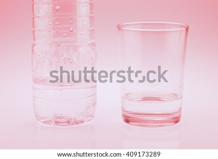 Plastic bottle and glass of drinking water on red tone. Global shortage of drinking water #409173289