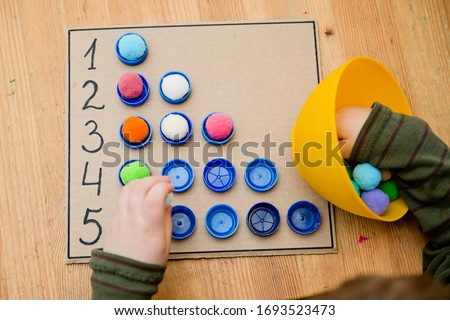 Plastic bottle caps. Put correct  amount pom poms  in cups. 5 minute carfts. DIY children home activity. Early education, counting game, fine motoric skills. #stay at home.