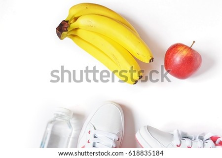 Plastic bottle of clean water, white sneakers, red apple and a bunch of yellow bananas. Trendy sports shoes and fruits. Flatlays. Image for blog and web site