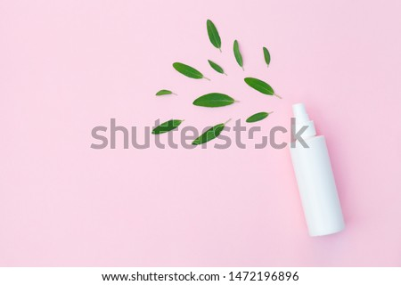 plastic bottle of facial moisturizing toner or hair spray and green herbal leaves isolated on pastel pink background, flay layout, top view, copy space, natural organic beauty product Foto stock ©