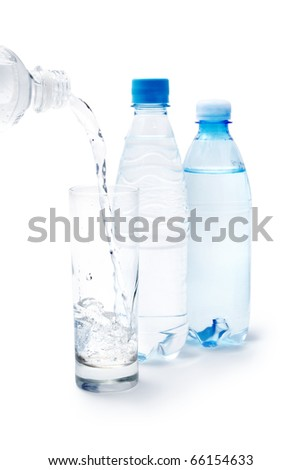 Plastic bottles and water pouring into the glass isolated on white