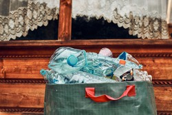 Plastic bottles collected in big container. Heap of plastic bottles, cups, bags collected to recycling. Concept of plastic pollution and too many plastic waste