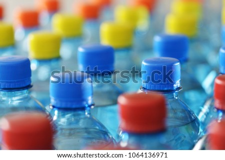 Plastic bottles of flavoured water with multi coloured bottle tops #1064136971