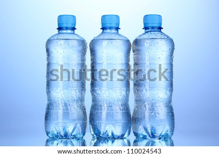plastic bottles of water on blue background