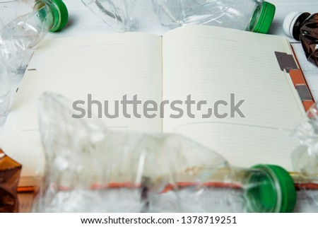 Plastic bottles on a background of a notebook with blank pages. Concept of caring for environment, recycling. Secondary plastic circuit. Environment pollution. Entering information about recycling.
