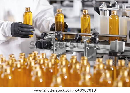 Plastic bottles with yellow liquid substance of shampoo, shower gel or soap standing in rows on assembly line at factory. Researcher in black gloves working at production line in modern laboratory