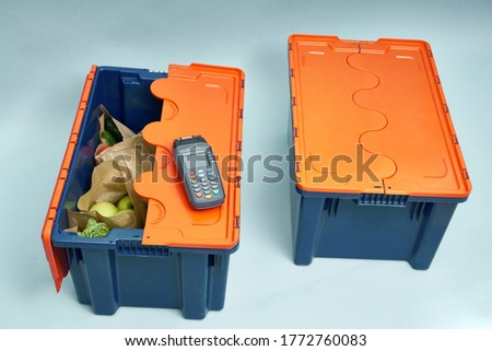 Plastic box with products. Food delivery in platinum boxes. Safe delivery. Storage of fragile goods