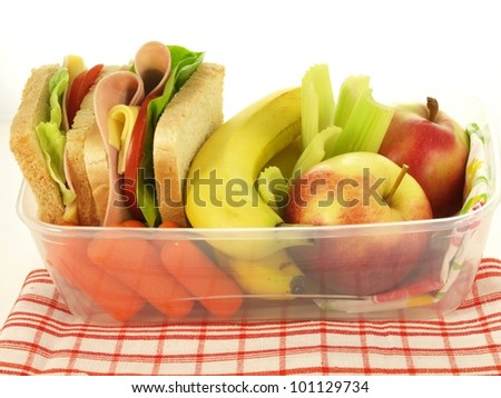 Plastic box with sandwiches and vegetables on a napkin