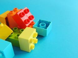 Plastic bricks, blocks, toy on bright blue background.