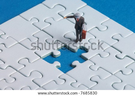 plastic business man walks on a puzzle