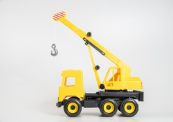 Plastic car. Toy model isolated on a white background. Yellow truck mounted crane.