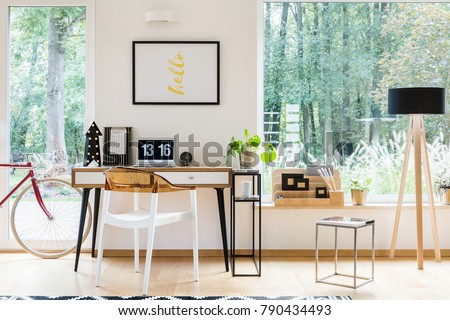 Shutterstock Plastic chair at desk with laptop and poster on white wall in home office with bike, lamp and stool