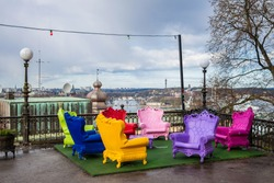 Plastic chairs in different colours. Comfortable chairs for outside leisure. Cheap chairs imitate rich or luxury. Bright furniture on open air. Place for your text. Chairs stand on roof. View on city