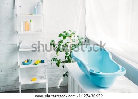 plastic childrens bathtub on stand in white modern room